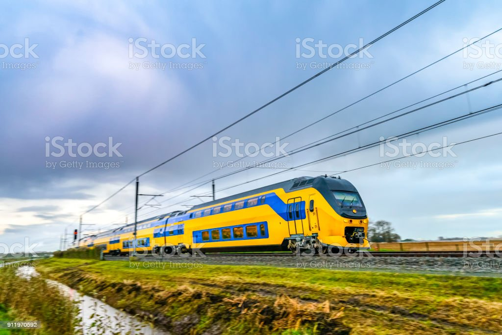 Train driving in a rural landscape during a dark day - foto stock