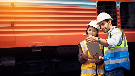 The Railway engineers wearing helmets and safety vests were chatting or meeting on an outdoor train track Beside the locomotive. Successful Rail logistics specialist setting up a transport system.