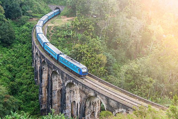 train goes over bridge - bahn reisen stock-fotos und bilder