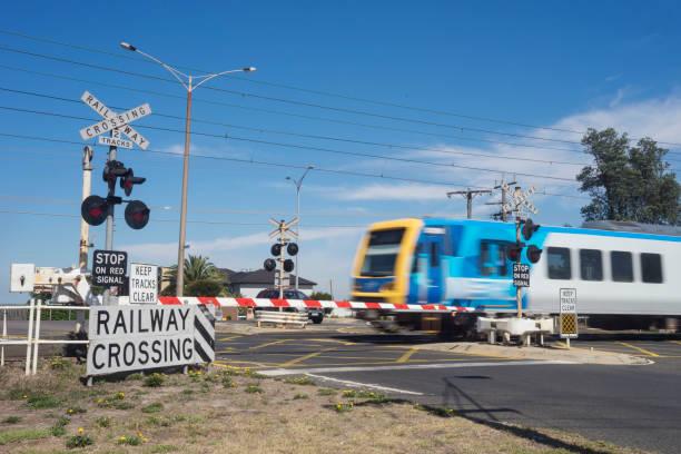 train en passant par le passage à niveau ferroviaire, melbourne - pont gênes photos et images de collection