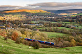 Passanger train passing through british countryside near greater Manchester, England.