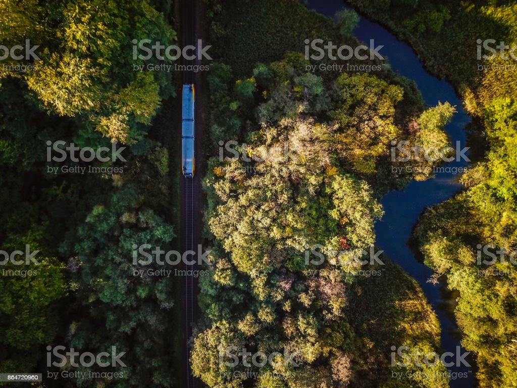 Train in nature Aerial shot of train running through forest in Copenhagen, Denmark.  Aerial view shot with drone. Above Stock Photo