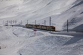 Kleine Scheidegg, Switzerland - April 4, 2014: Kleine Scheidegg, Switzerland - Yellow train on track with snow on the mountain, the train that is carrying passengers to the ski slopes in the Swiss Alps. Ski tracks can be seen in the snow in this ski resort and people are on the snow