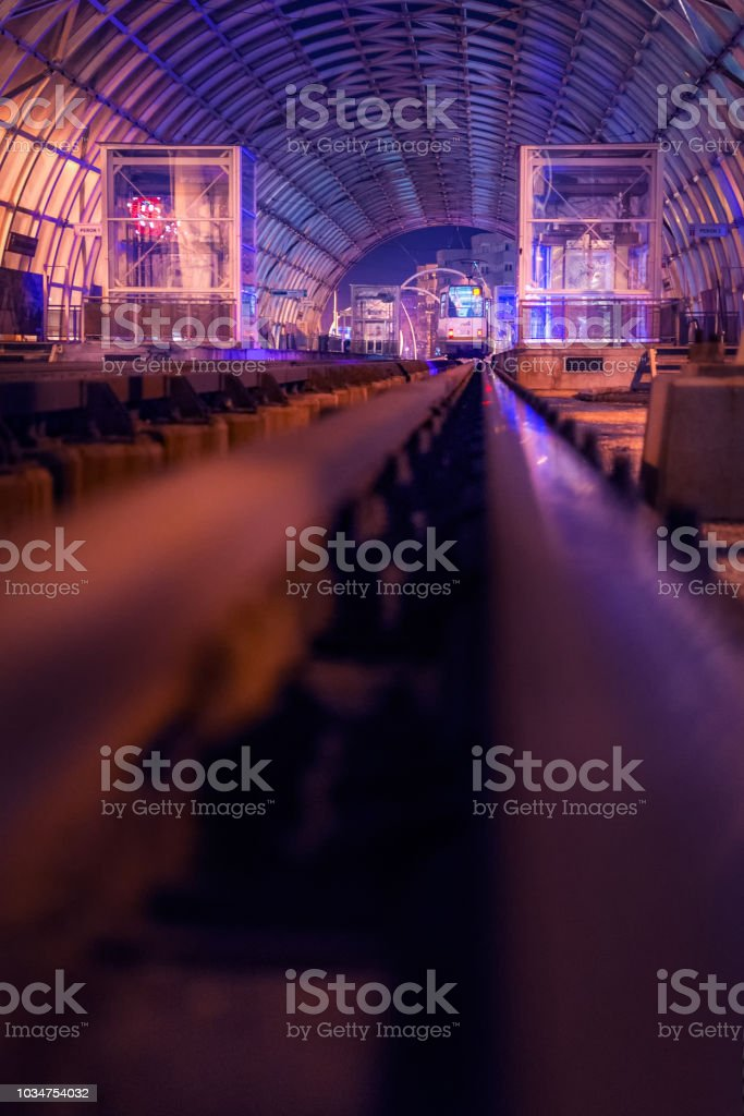 Train in the station by night in a city with a low ground from the train line vantage point stock photo
