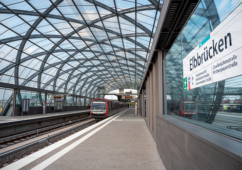 A train (of the Hamburg Hochbahn service) in  the subway station Elbbrücken on a sunny day at September 11th 2020 in the new quarter Hafen City of Hamburg, Germany.