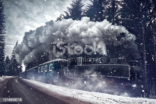 amazing shot of train in the winter time in motion with dense smoke.