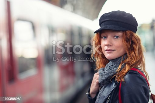 Portrait of a young woman standing on a station platform as a train arrives.