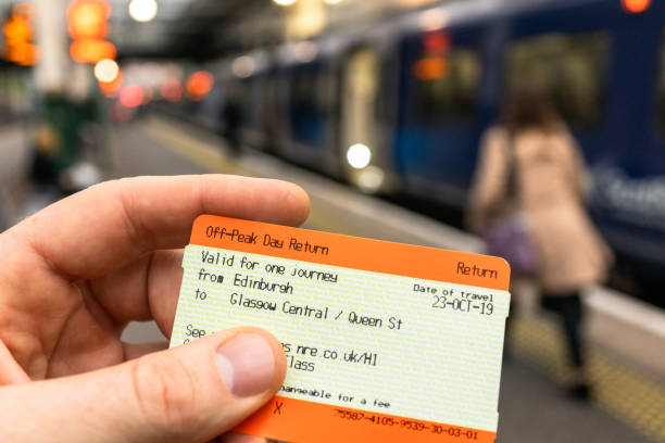Train journey from Edinburgh to Glasgow Edinburgh, Scotland - Close-up of a train ticket between Edinburgh Waverley and Glasgow, with the Scotrail train in the background. train ticket stock pictures, royalty-free photos & images