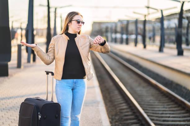 tren geç, geciken, iptal edilen veya programın gerisindeyiz. time ve izle karışık kadın platformu beklerken. - sefer tarifesi stok fotoğraflar ve resimler