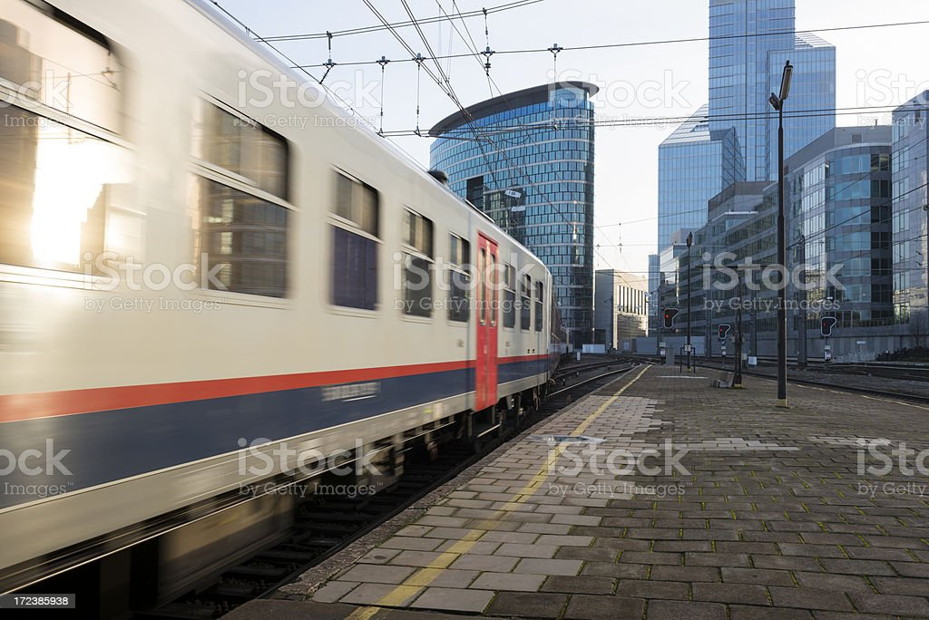 Train leaving station at sunset stock photo