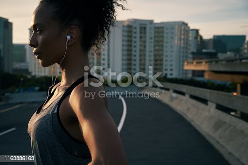 Cropped shot of an attractive young woman wearing earphones and standing outside in the city after her morning run