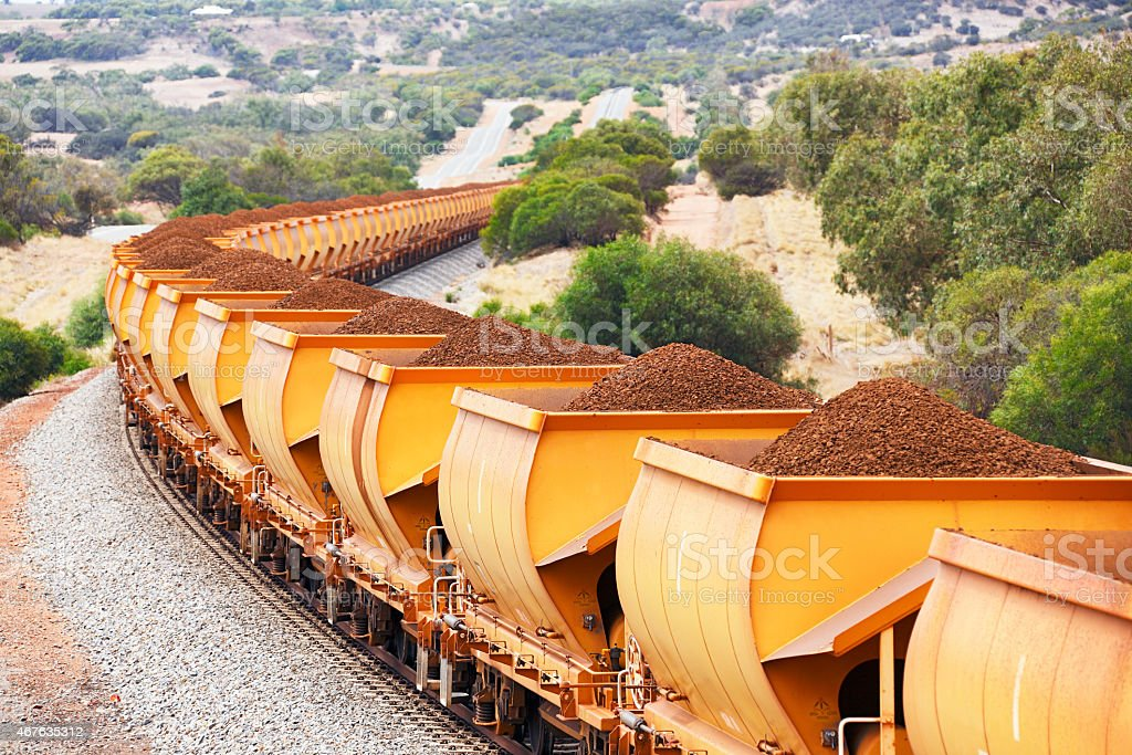 Train loaded with brown hematite iron ore in hills stock photo