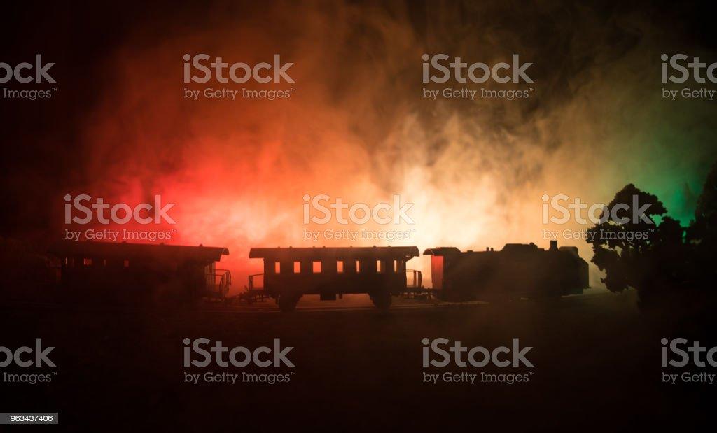 Tåget rör sig i dimman. Antika ånglok i natt. Natt tåg flytta på järnvägen. tonad dimmigt brand bakgrund. Horror mystiska scen. - Royaltyfri Antik Bildbanksbilder