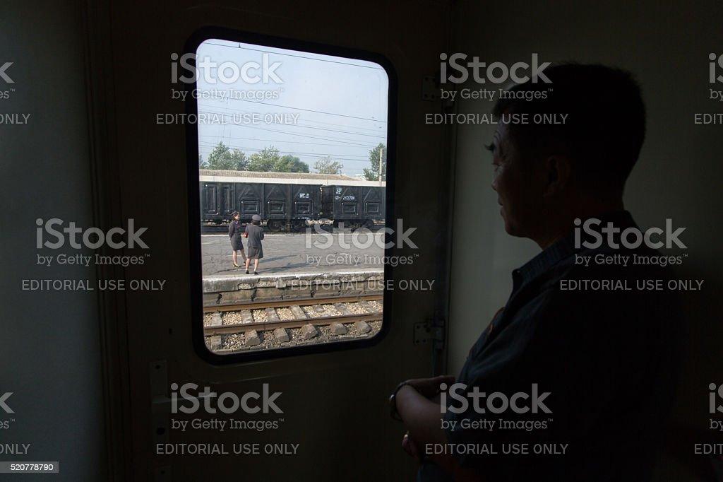 DPRK train (Dandong-Pyongyang): North Korean watches women at station stock photo