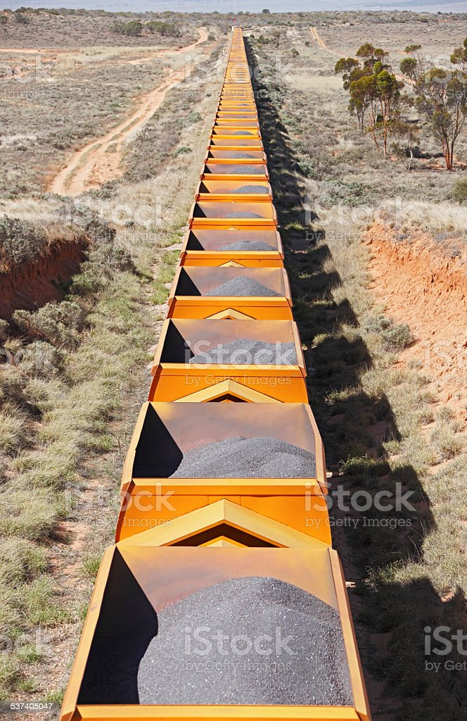 Train of bright yellow freight cars with processed iron ore stock photo