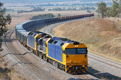 Three diesel-electric locomotives work hard uphill and around an s-curve with a trainload of containerised ore on its way from mine to port.  Two large locomotives with a small one in the middle – all identification marks and logos removed.  Unidentifiable people.