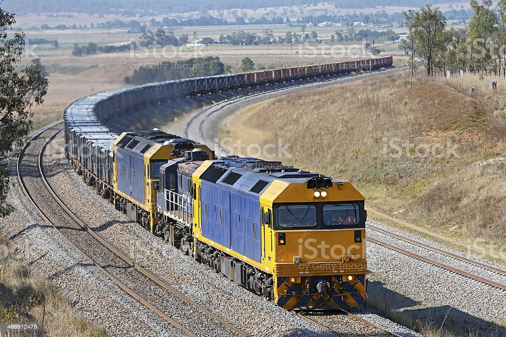 Train of containers loaded with ore rounding a curve stock photo