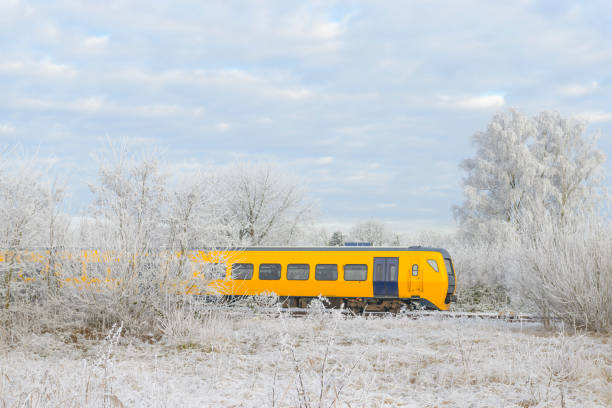 Train of the Dutch Railways driving through a frozen winter landscape stock photo