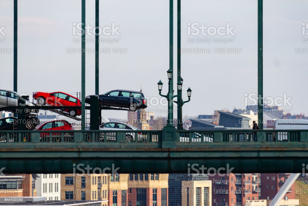 Train of transported new cars crossing the Tyne Bridge at Newcastle Quayside on a cloudy day stock photo