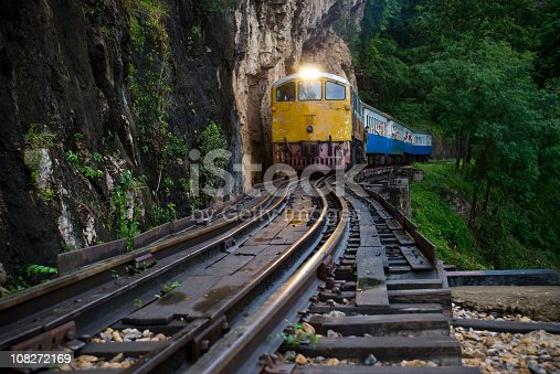 A train passes over the Krasae Viaduct at dusk near Kanchanaburi, Thailand.  This track is part of the infamous Death Railway, built during WWII. Passengers are looking out the windows.