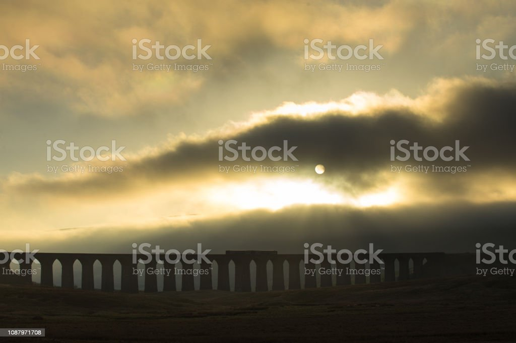 Train on Middle of Ribblehead Viaduct on Foggy Evening stock photo