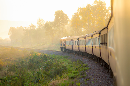 Train on Railroad track during autumn foggy morning.