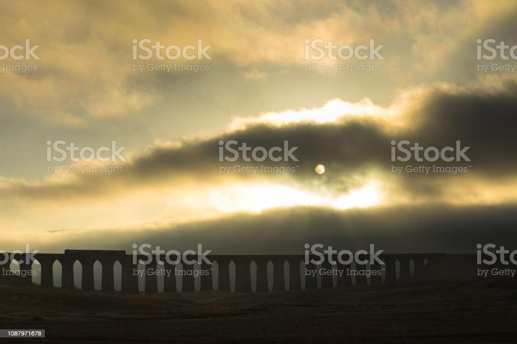 Train on Ribblehead Viaduct on Foggy Evening stock photo