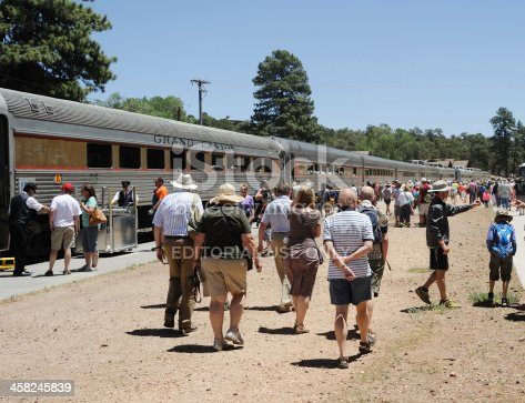 Grand Canyon Village, United States - June 19, 2013: Passengers leaving the Grand Canyon Railway's 11.45 arrival from Williams, Arizona, at the depot at Grand Canyon Village. They will disperse to view or walk the South Rim, to go on bus tours or to head for the airfield and a flight over the Canyon. The journey from Williams is 65 miles long and takes 2 hours, 15 minutes. Unidentified train crew and passengers.