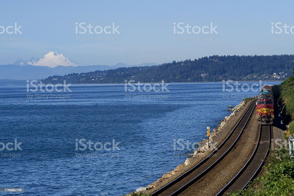 Train on Tracks Going By Pacific Ocean Mount Baker Background royalty-free stock photo