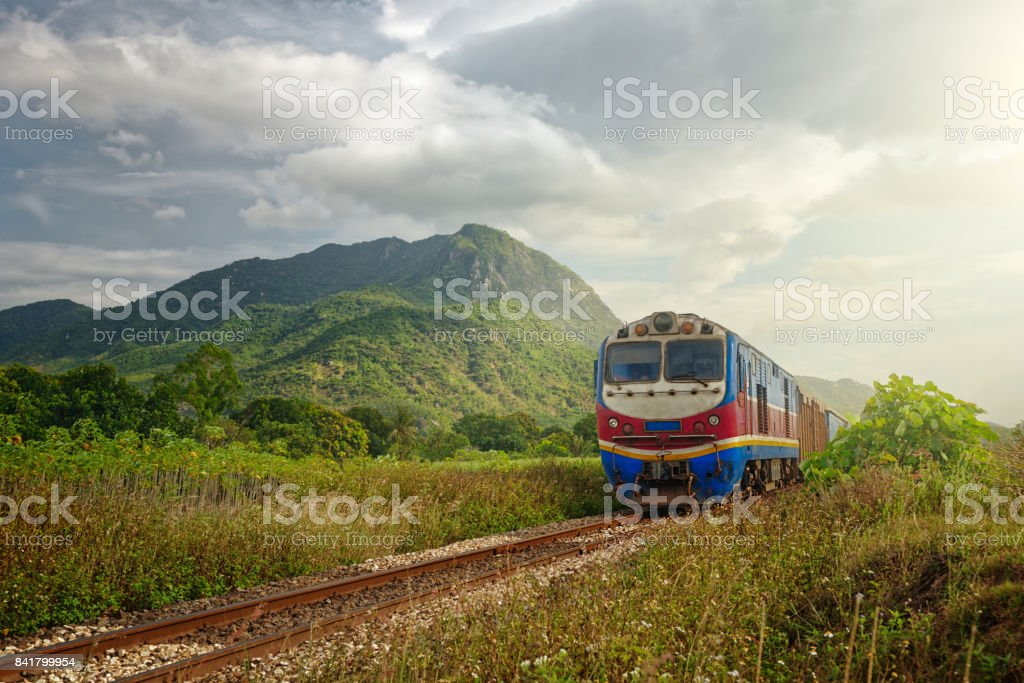 Train passing at sunset against the background of mountains stock photo