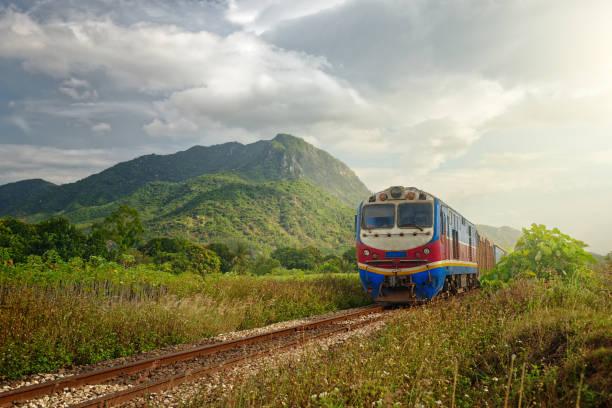 tåg passerar vid solnedgången mot bakgrund av berg - järnvägsvagn tåg bildbanksfoton och bilder