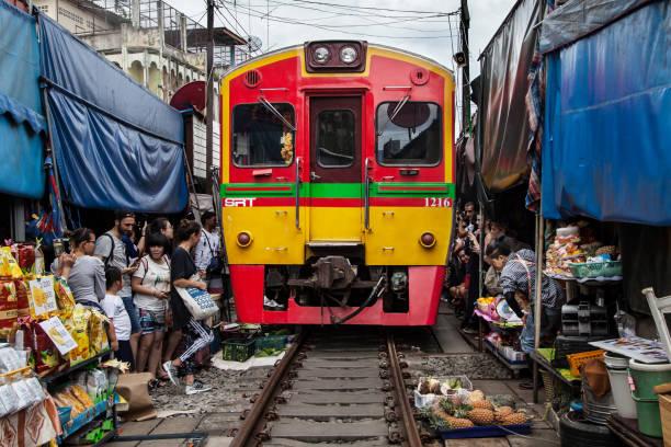 Train passing through the Railway Market Maeklong stock photo