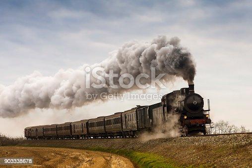 Vintage black steam train running on railway in countryside