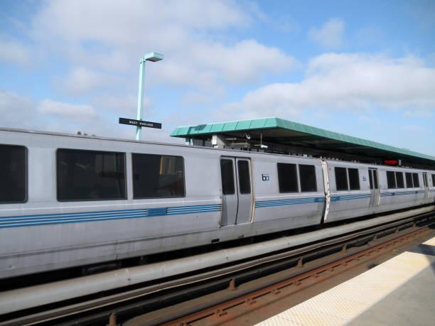 bart train zieht in west oakland station - bart stock-fotos und bilder