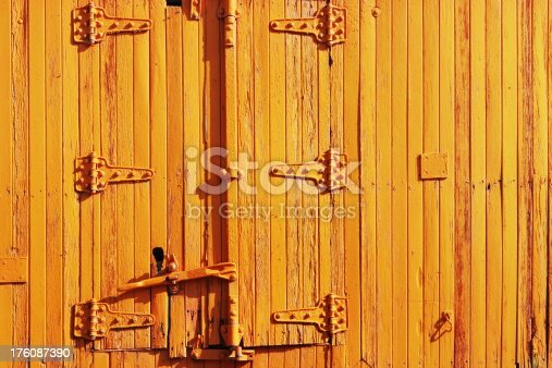 Vintage railroad train railcar wood plank siding and door with hinge and handle hardware entirely painted with yellow enamel.
