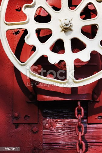 Railroad train hand brake wheel and chain on vintage freight railcar with interesting lighting.