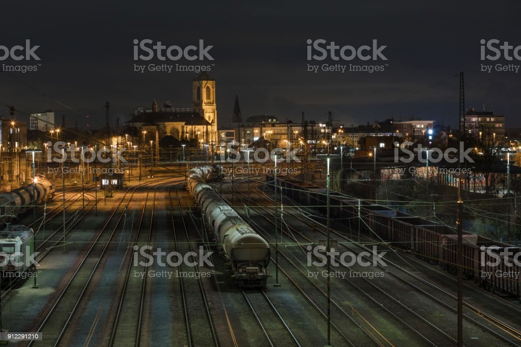 Train Rails With Trains At Night With View On Church At Neuss stock photo