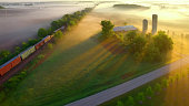 Train rolls through foggy rural landscape at dawn as the long shadows loom between sunbeams; aerial view.