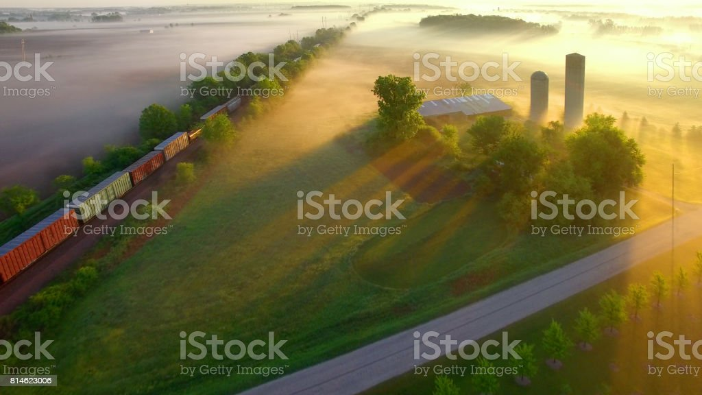 Train rolls through foggy rural landscape at dawn. stock photo