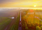 Freight train rolls through foggy rural landscape at sunrise, aerial view, breathtaking scenic beauty.