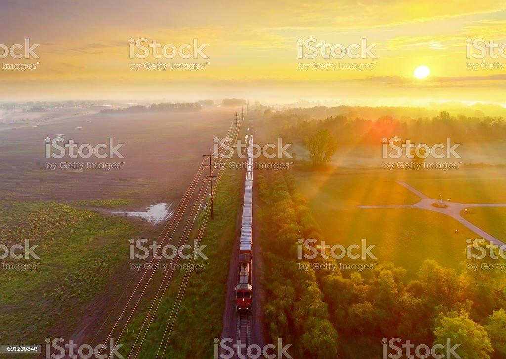 Zug rollt durch neblige Landschaft bei Sonnenaufgang, Luftbild – Foto