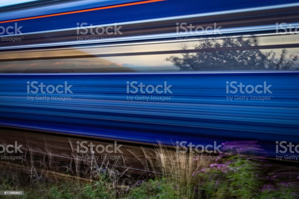 Train speeding past and captured with motion blur stock photo