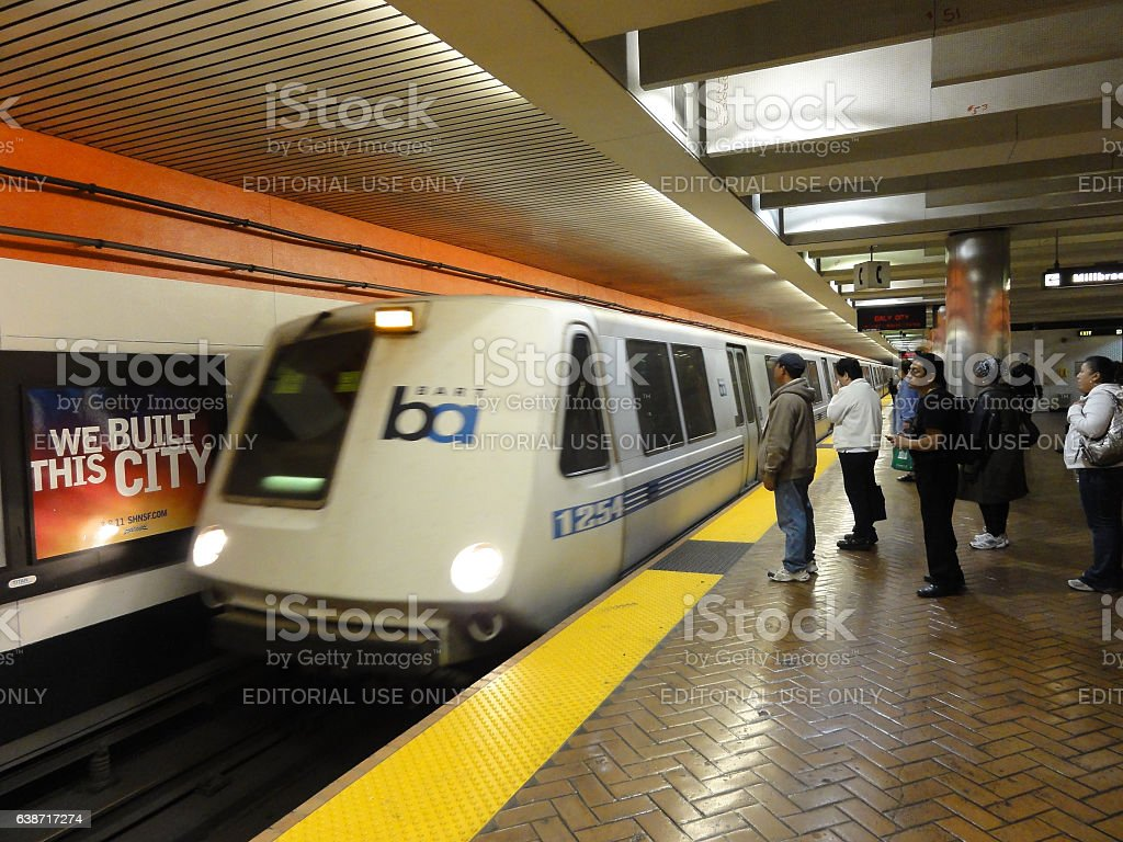 BART Train speeds into station platform with people waiting stock photo