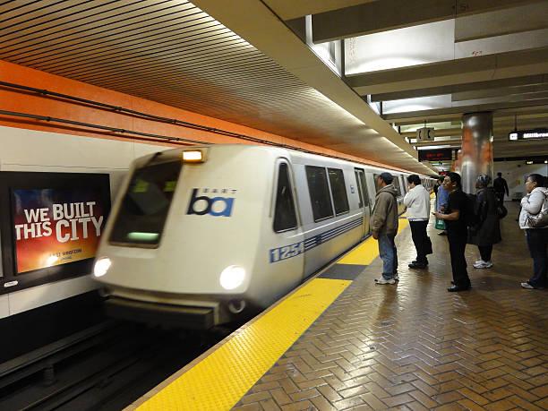 bart train speeds into station platform with people waiting - bart stock-fotos und bilder