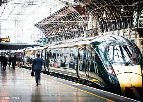 Motion blurred anonymous people walking inside large railway terminus platform