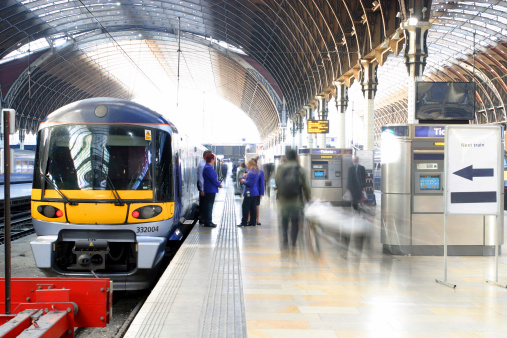 A train at a train station. Blurred station staff and commuters on the platform.