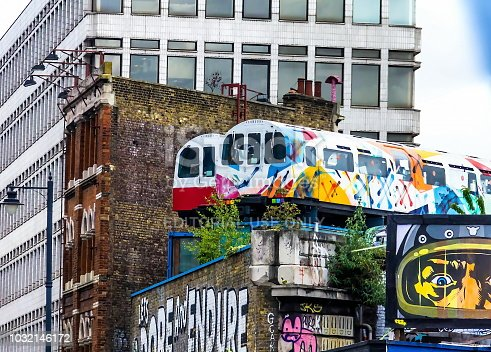 London,UK - June 9, 2015: Train Station. Two cars of a passenger train painted with bright colors. Vandalism drawings on transport. Train on the platform
