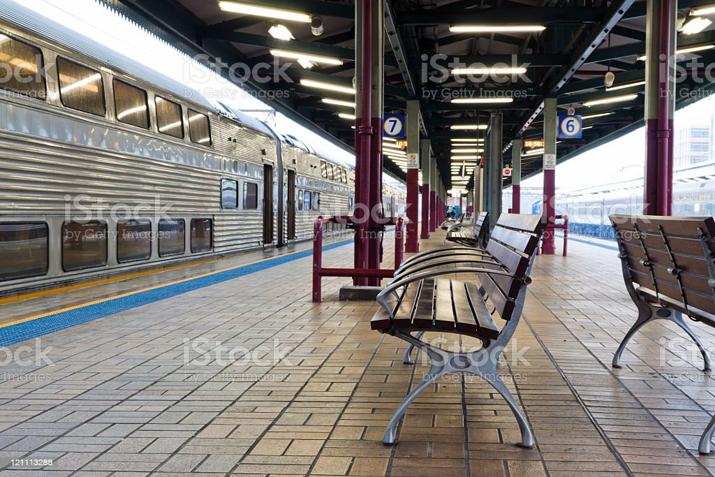 Train station with seats and waiting train in rainy day stock photo