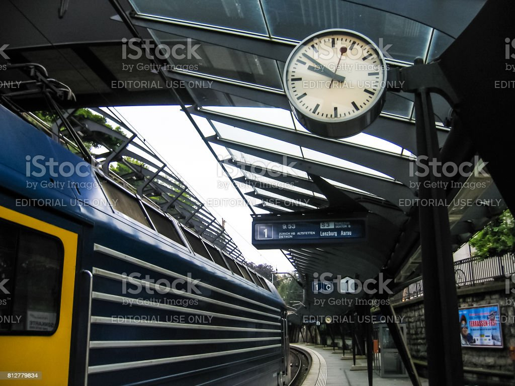 Train station with signs for cities and clock showing time stock photo