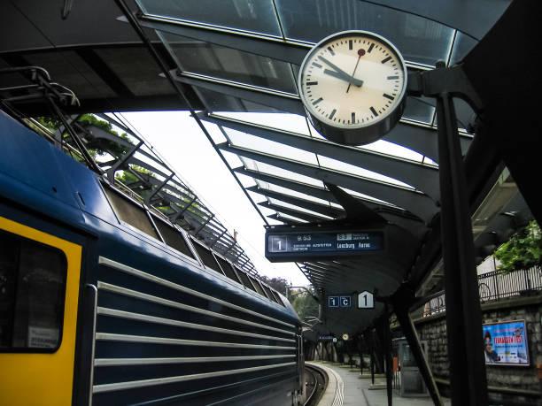 Bahnhof mit Anzeichen für Städte und Uhr Zeit anzeigen – Foto